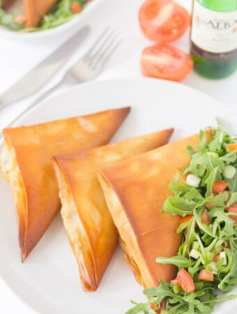 Three tomato basil mozzarella filo parcels on a plate with salad. A bottle of wine, halved tomato and knife and fork to the side as decoration.