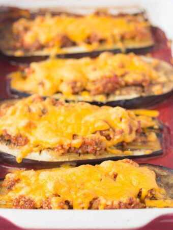 Four halved baked aubergine with red pesto and cheese.