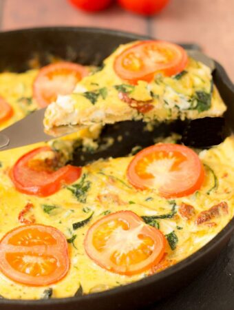A slice of courgette and sundried tomato frittata being lifted from the skillet it was cooked in.