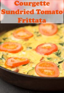 CLose up of a skillet of cooked courgette and sundried tomato frittata. Pin title text overlay at top.