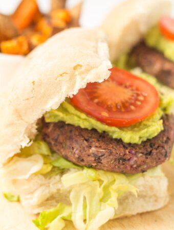 A quick and easy black bean burger in a burger bun topped with avocada and a sliced tomato.