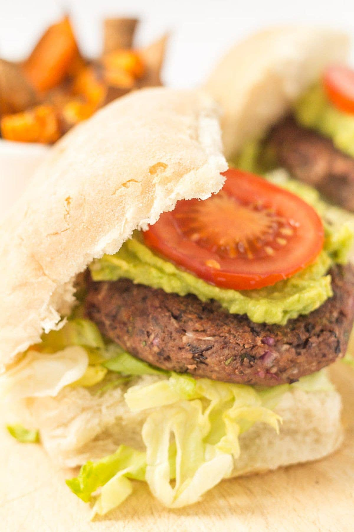 A quick and easy black bean burger in a burger bun topped with guacamole and a sliced tomato.