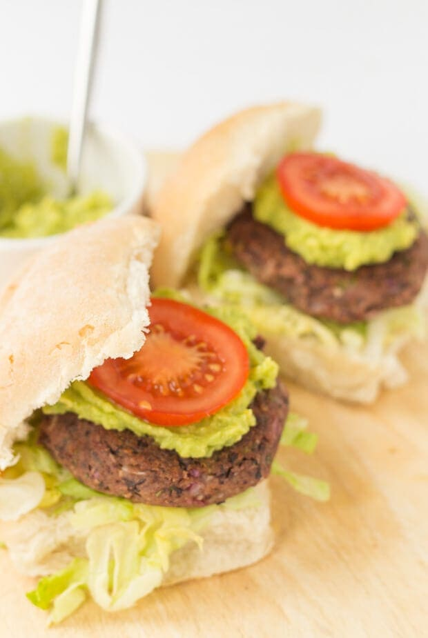 Two quick and easy black bean burgers in burger buns topped with guacamole and a sliced tomato.