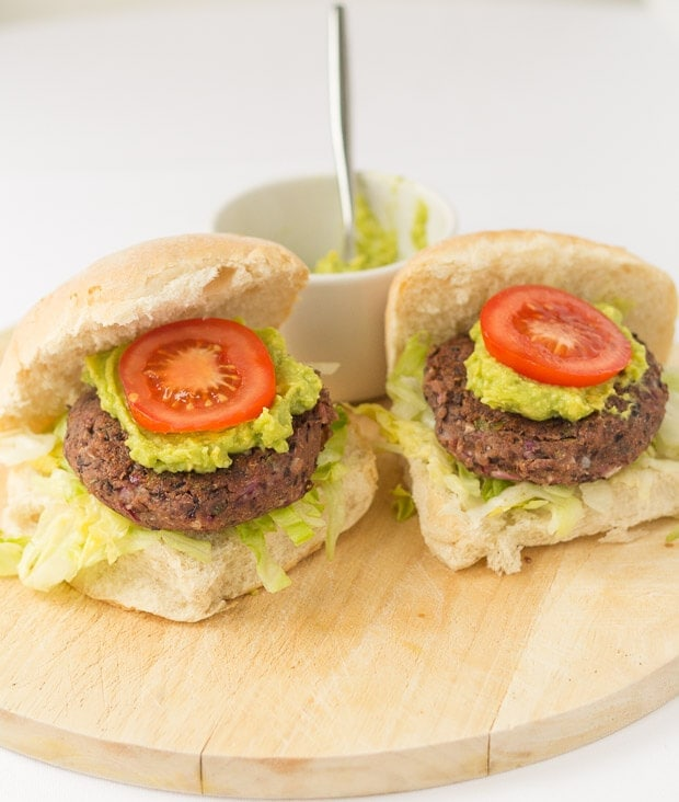 Close up of two quick and easy black bean burgers in burger buns on a bread board with a dish of guacamole in the background with a spoon in.