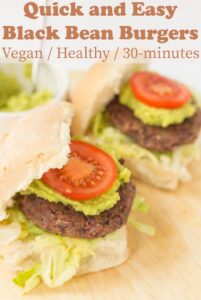 Two delicious quick and easy black bean burgers served on burger buns topped with guacamole and a tomato.