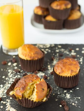 Three raisin oat breakfast muffins on a black slate. Glass of orange juice and a stack of the muffins on a plate in the background.