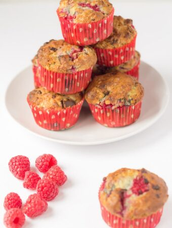 A stack of dark chocolate raspberry muffins on a white plate in the background. Raspberries at the left foreground and a single muffin to the right foreground.