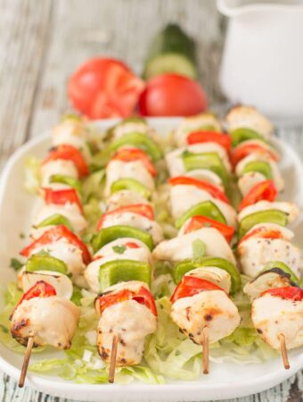 Four honey mustard chicken skewers on a serving platter with two tomatoes, a cucumber and a jug in the background.