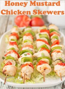 Grilled honey mustard chicken skewers laid out on a serving dish.