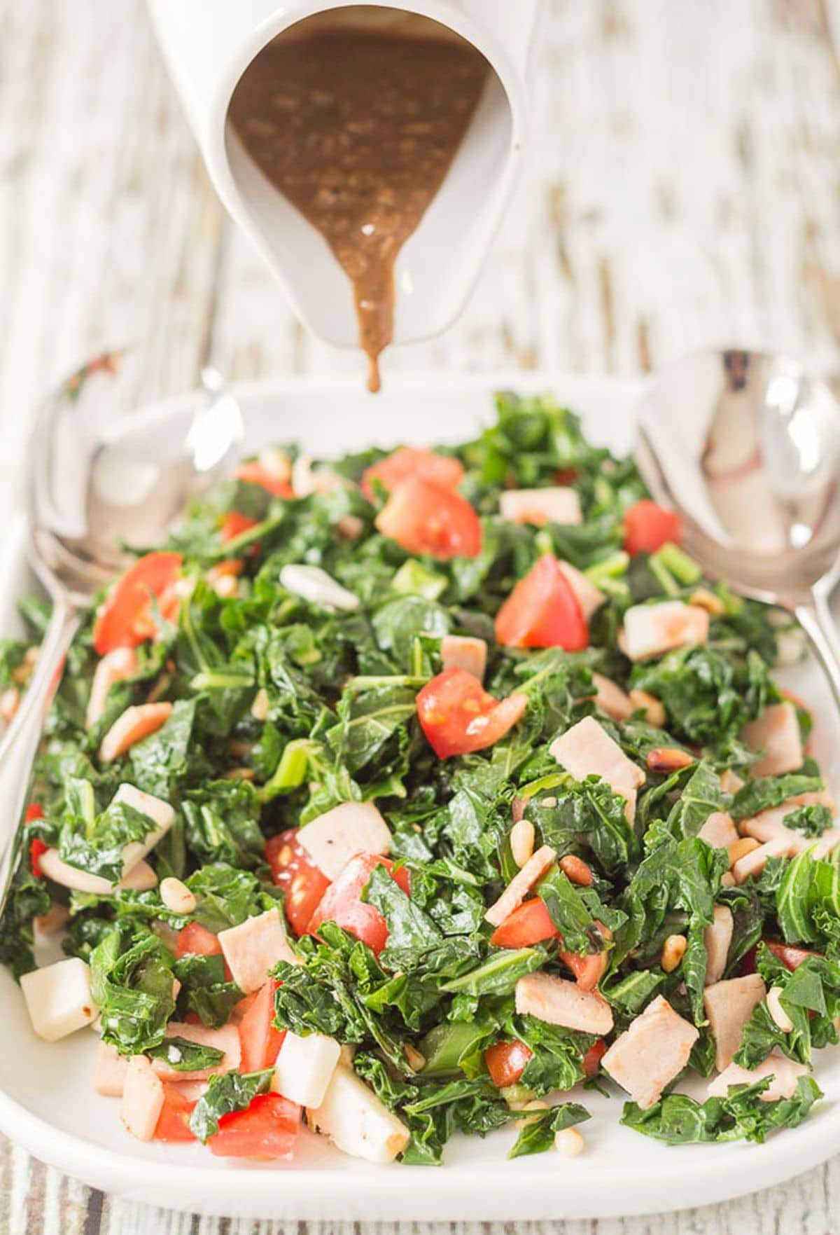 Balsamic dressing being poured from a jug onto a platter of kale and turkey bacon salad.