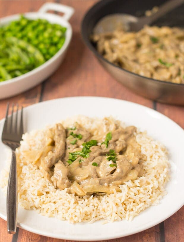 Quick healthy beef stroganoff served on a bed of wholegrain rice garnished with parsley. A side dish of green beans and the the cooking pan in the background.