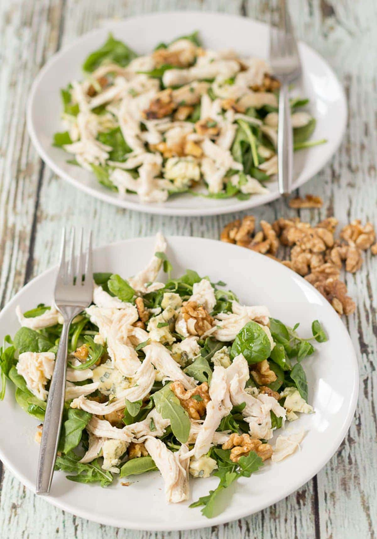 Two plates of chicken walnut and blue cheese salad one in front of the other with forks on and walnuts for decoration in between.