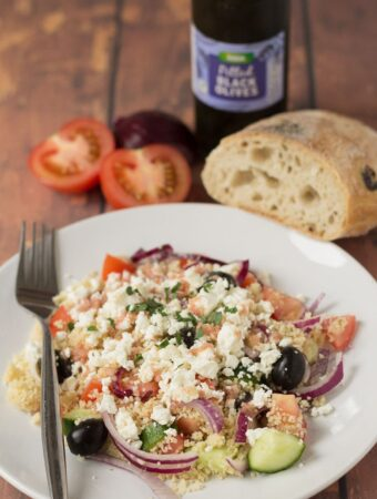 A plate with couscous Greek salad served on it and a fork to the side. Part of a ciabatta loaf, a sliced tomato and jar of olives in the back for decoration.