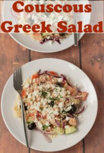 A plate with couscous Greek salad served on it and a fork to the side. Pin title text overlay at top.