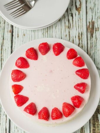 Birds eye view of a whole no bake strawberry mousse cheesecake decorated around the edge with halved strawberries. Serving plates and forks at the top.