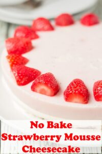 Half a no bake strawberry mousse cheesecake decorated around the edge with halved strawberries. Pin title text overlay at bottom.