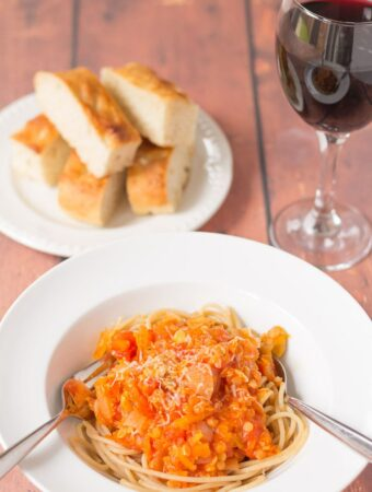 A plate of red lentil bolognese served with spaghetti and a fork and spoon in. Slices of ciabatta on a plate and a glass of wine in the background.