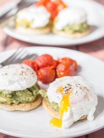 Two plates of smashed avocado and poached eggs on muffins, one in front of the other. Each plate served with cherry tomatoes and a knife and fork on.