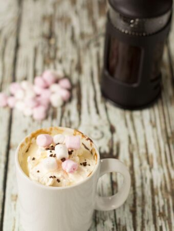 Americano coffee mug cake decorated with marshmallows and a cafetiere in the background.