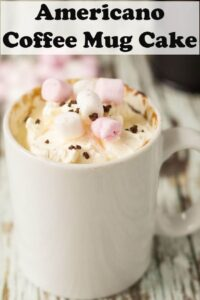 Americano coffee mug cake decorated with mini marshmallows with a cafetiere in the background.