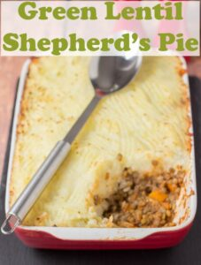 Green lentil shepherds pie just taken out of the oven with a portions taken out of it and a spoon layed over it.