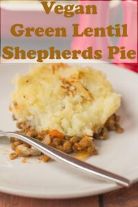 A portion of vegan green lentil shepherds pie served on a plate with a fork to the left hand side. Pin title text overlay at top.