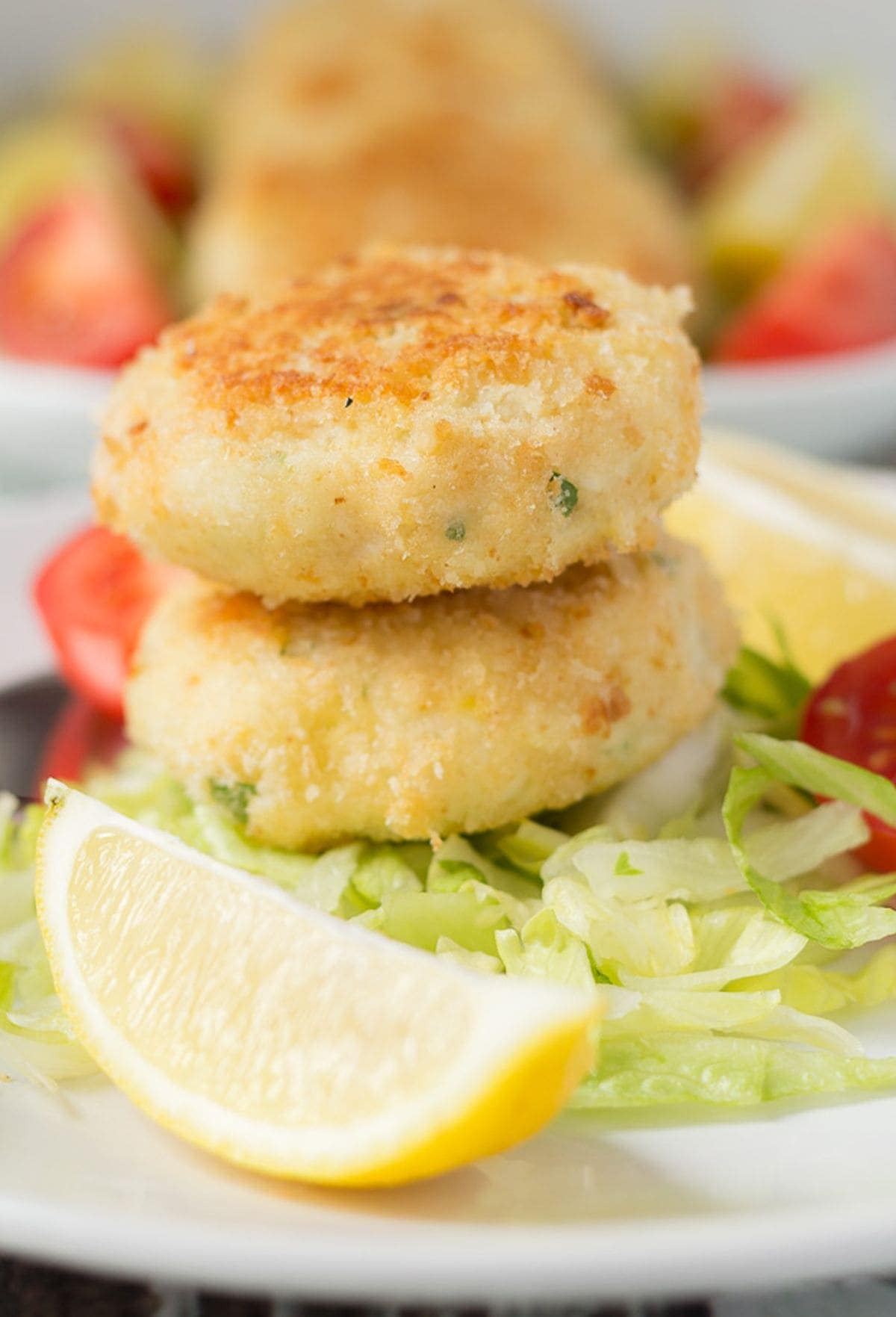 Two quick healthy fish cakes stacked on a bed of iceberg lettuce with a lemon wedge in front.