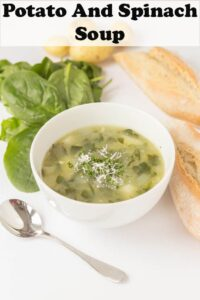 A bowl of potato and spinach soup with a spoon beside the bowl and bread and spinach surrounding it.