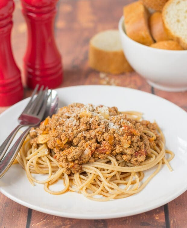 Close up of a plate of Quorn bolognese with spaghetti. Fork and spoon to the side. A bowl of sliced baguette and salt and pepper cellars in the background.