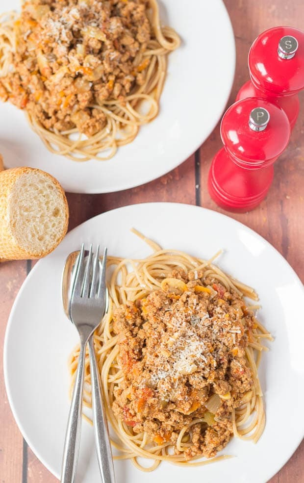 Birds eye view of two plates of Quorn spaghetti bolognese. Salt and pepper cellars and a slice of garlic bread in between.