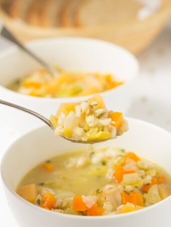 Two bowls of Scottish vegetable soup one in front of the other. A spoonful of soup being lifted from the front bowl.