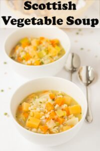 Two bowls of Scottish vegetable soup with soup spoons to the right hand side. Pin title text overlay at top.