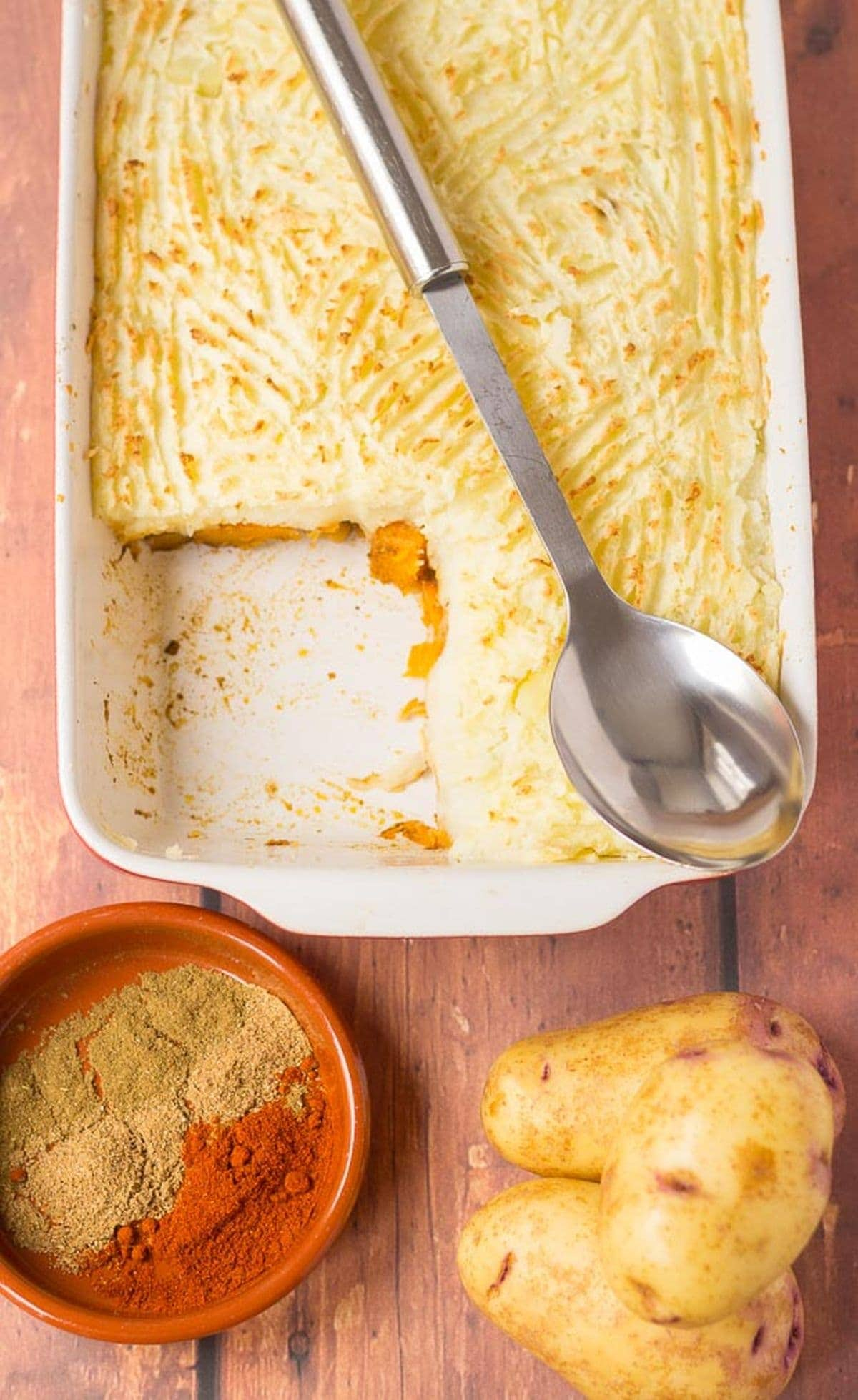 Birds eye view of spiced butternut squash bake casserole with a spoon lying over the top and a portion taken out. Potatoes and a dish of spices at the bottom.