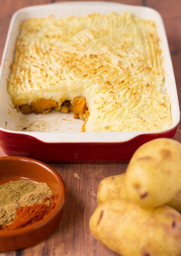 Spiced butternut squash bake in the background. Potatoes and a dish of spices in the foreground.