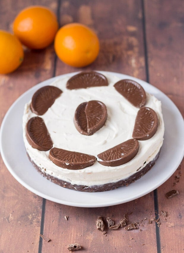 No bake chocolate orange cheesecake on a plate decorated with chocolate segments and three oranges for decoration in the background.