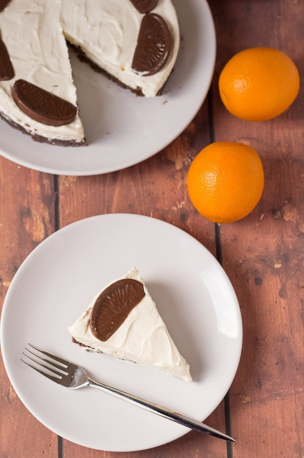 Birds eye view of a slice of no bake chocolate orange cheesecake served on a plate with a fork. Rest of the cheesecake at the top of the picture with two oranges to the side as decoration.