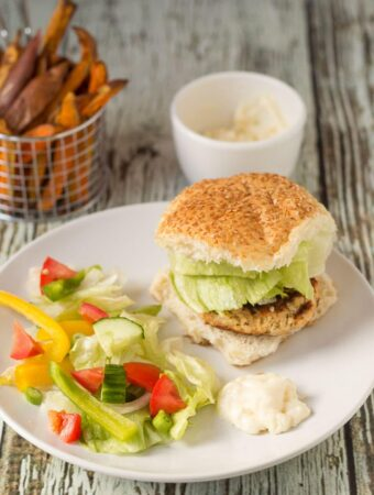 A quick healthy salmon burger served in a bun on a plate with salad. Pot of mayonnaise and basket of sweet potato fries in the background.