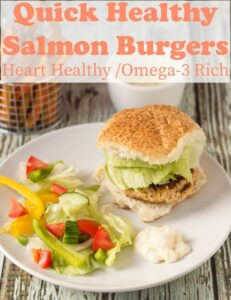 A quick healthy salmon burger served in a burger bun with a light side salad on a plate.