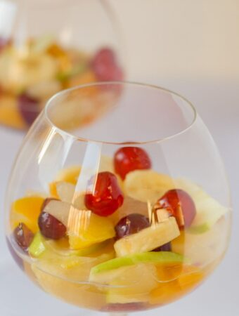 Two glasses of boozy fruit salad one in front of the other.