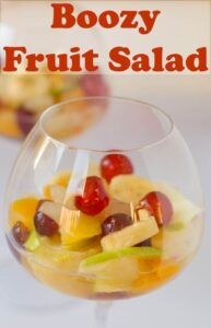A glass of boozy fruit salad ready to eat.