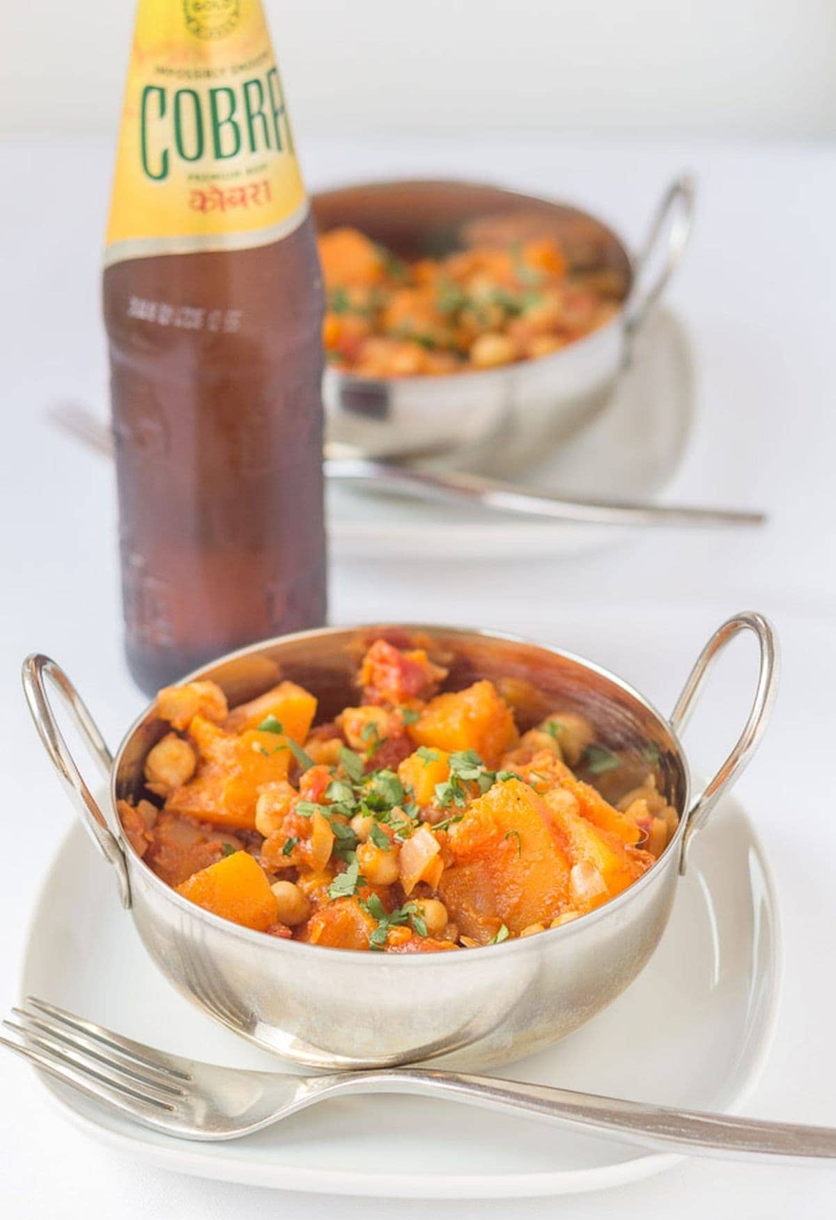 Two balti dishes with chickpea and butternut squash curry in, sitting on plates with a fork to the side. A bottle of lager in between.