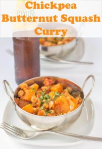 Chickpea and butternut squash curry served in a balti dish with a bottle of Indian Cobra larger in the background.