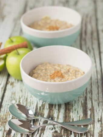 Two bowls of apple spice porridge one in front of the other. Two apples and cinnamon sticks in between and two spoons in the foreground.