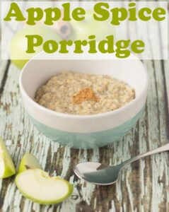 Bowl of delicious cooked apple spice porridge ready to eat. With a spoon in front and slices of apple.
