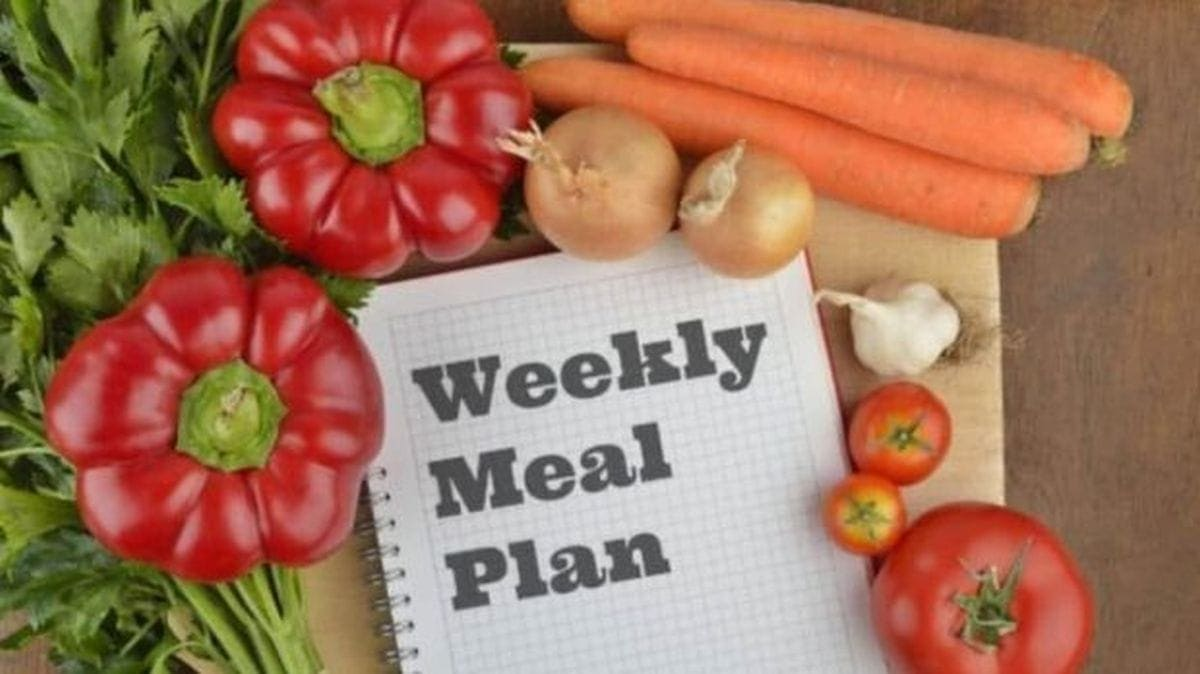 Weekly meal plan journal in centre of picture surrounded by vegetables.
