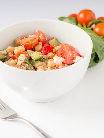 A bowl of Mediterranean chickpea salad with a fork beside. Basil leaves and cherry tomatoes in the background.