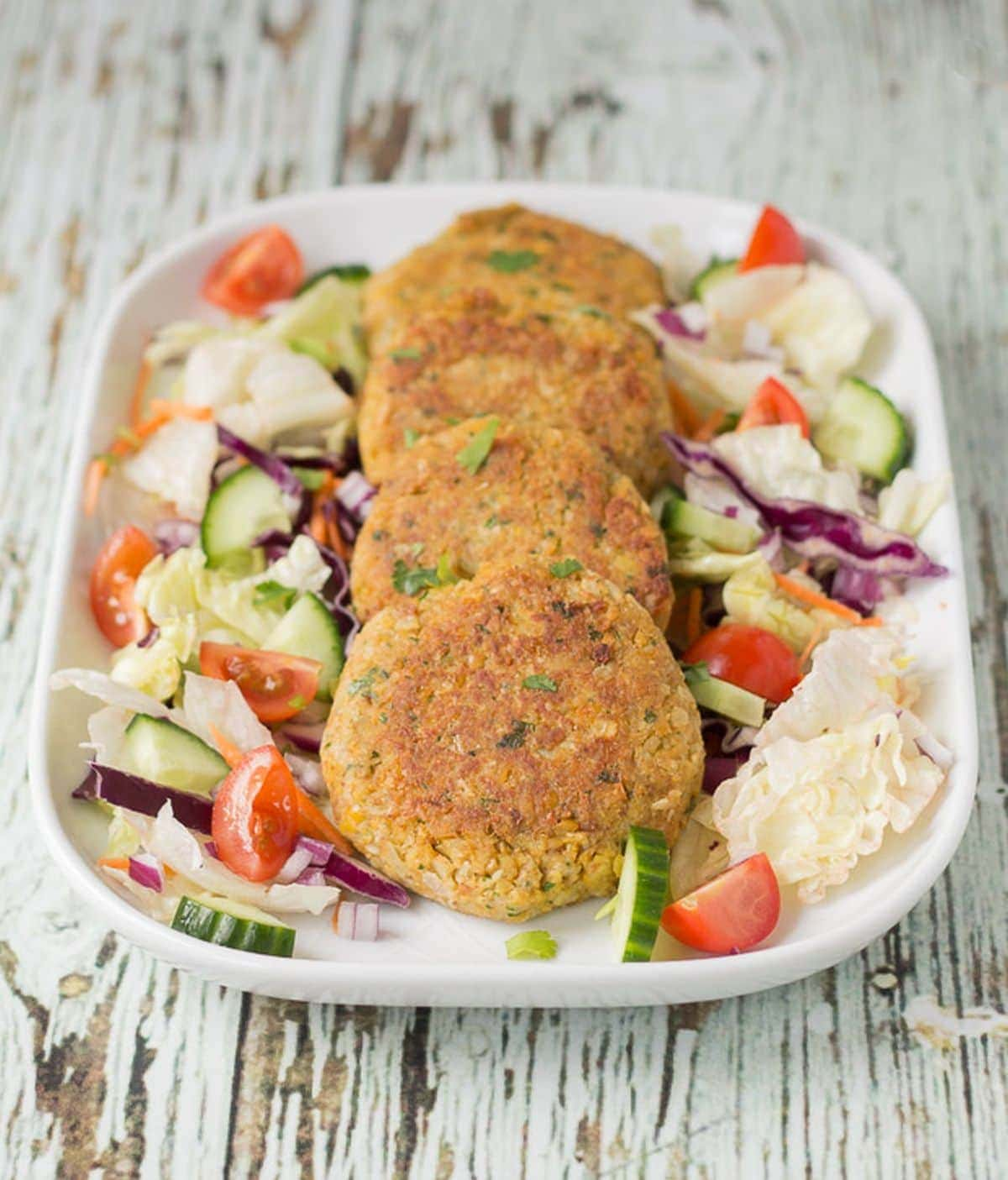 Four quick healthy chickpea cakes arranged on a platter dish surrounded by a salad of lettuce, cucumber and sliced tomatoes.