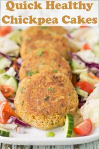4 quick healthy chickpea cakes laid in a line facing forward on a white rectangular serving plate. Garnished around the chickpea cakes with salad.