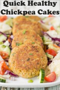 Four quick healthy chickpea cakes arranged on a platter dish surrounded by a salad. of lettuce, cucumber abd sliced tomatoes. Pin title text overlay at top.