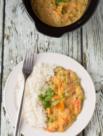Birds eye view of a plate of slow cooker sweet potato and vegetable curry served with rice and a fork to the side. Rest of the recipe in slow cooker dish at the top.